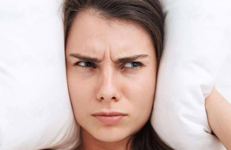 como hacer para no roncar mientras duermo: mujer con la almohada en la cabeza proque los ronquidos no le dejan dormir